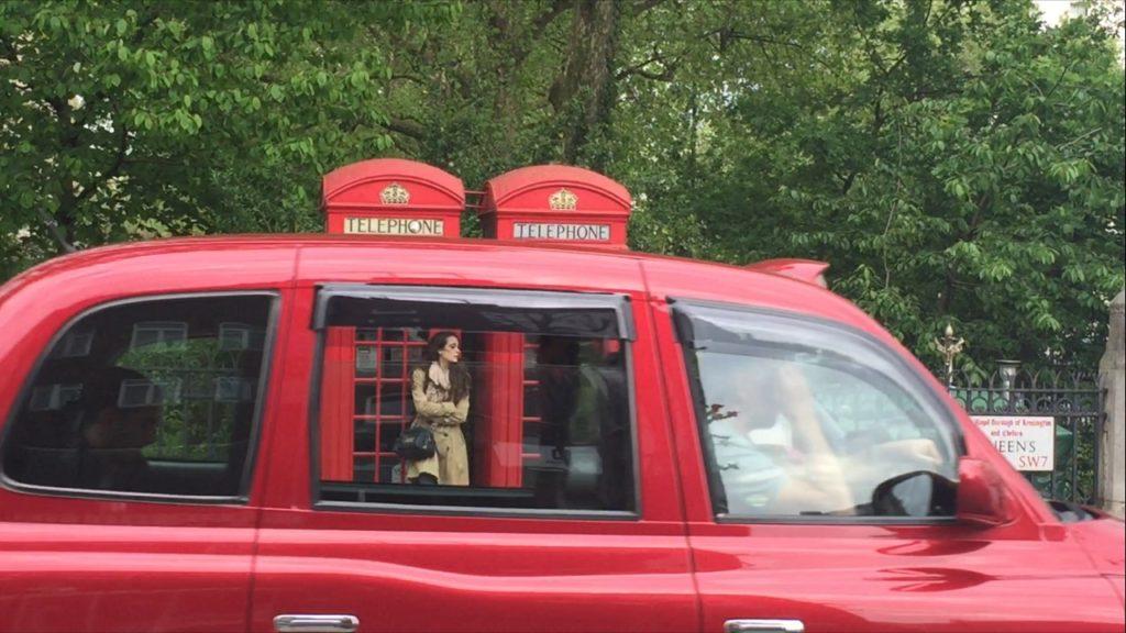 io accanto ad una cabina telefonica a londra, mentre passa un taxi