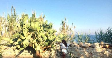 sabrina (ragazza mora, lunghi capelli ricci, in mise bianca poggiata su un muretto a secco, come sfondo li mare