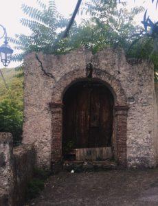 antico portale in rovina a maratea. albero cresciuto dietro la porta che si intravede dall'alto