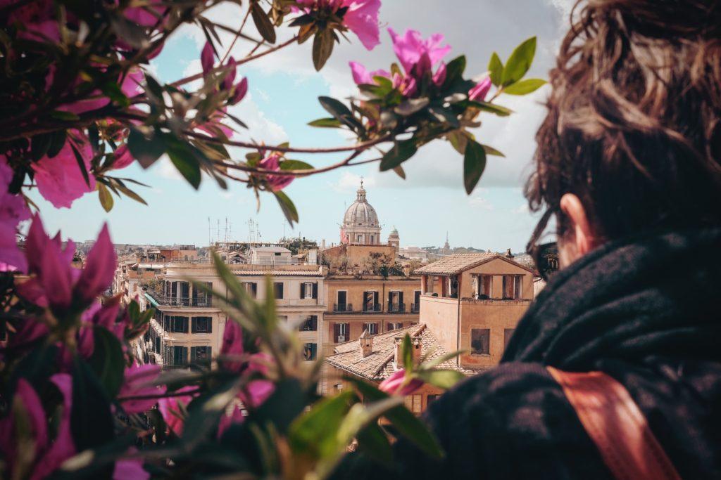 ragazza di spalle, capelli ricci legati, guarda scorcio di roma panoramica.