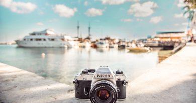 macchina fotografica nikon in primo piano e crociere e porto sullo sfondo.