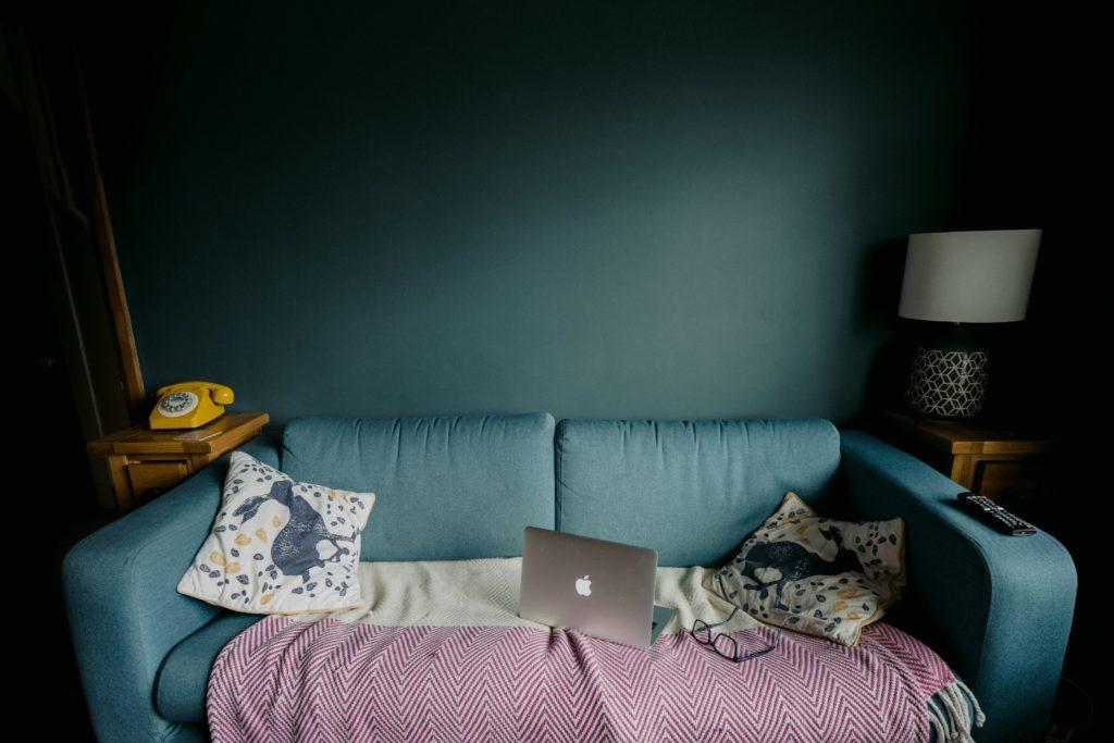 divano verde su parete azzurra con computer e coperta - lavorare da casa senza imbruttirsi