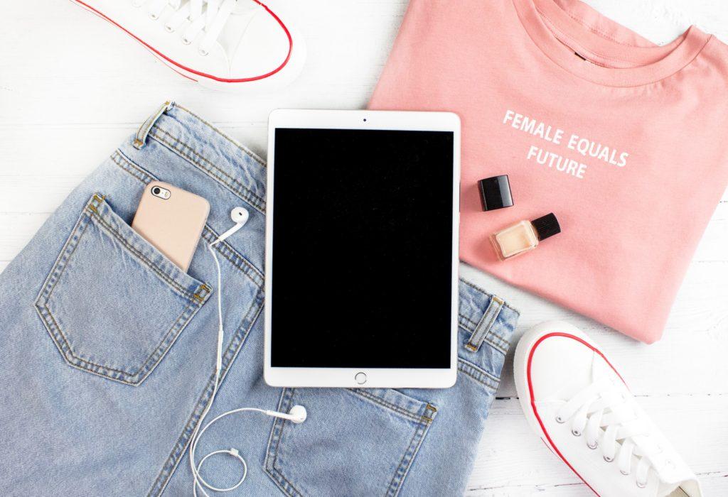 tablet su un paio di jeans e maglione rosa e scarpe da tennis
