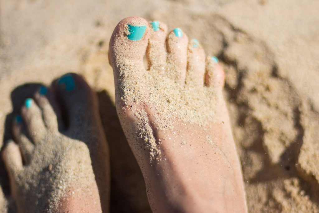 piede con smalto azzurro su spiaggia bianca