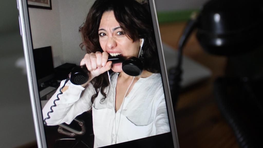 Sabrina morde una cornetta e lo si vede dallo schermo di un iphone_errori video chiamate