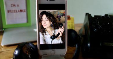 sabrina ripresa nello schermo di un iPhone, con una cornetta di antico telefono analogico in mano_Sfondo di una scrivania_video chiamate di lavoro_errori