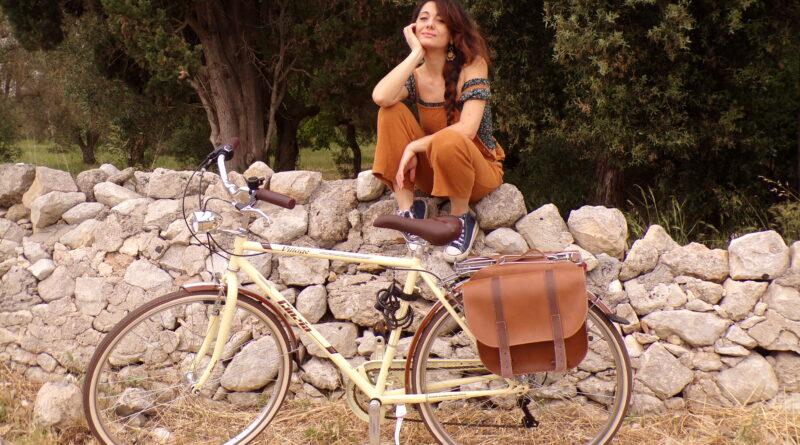 Sabrina su un muretto a secco davanti alla sua bici - viaggio in bici in Italia - itinerari