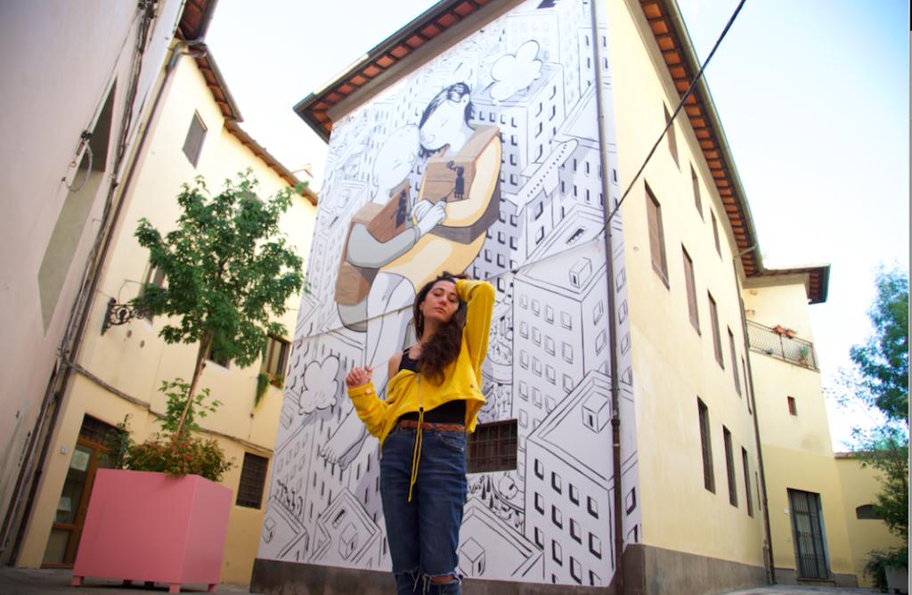 sabrina con jeans, maglia gialla in tinta con il murales alle sue spalle