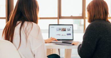 ragazze di spalle lavorano ad un computer accanto ad una finestra - agenzia immobiliare online_blog