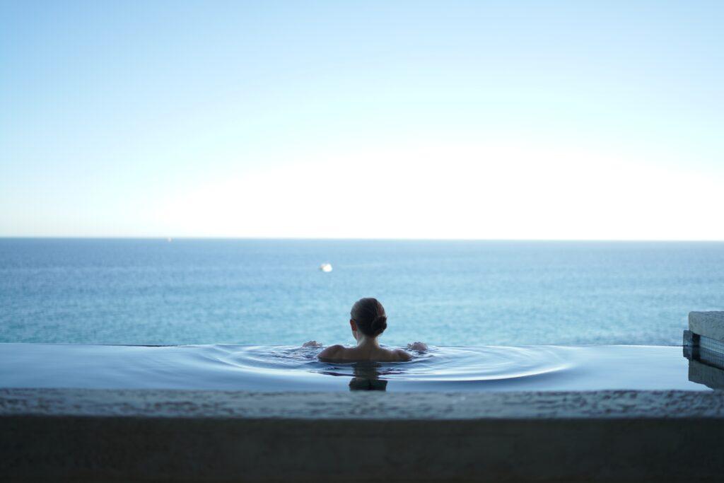 ragazza di spalle in una piscina sul mare in vista panoramica