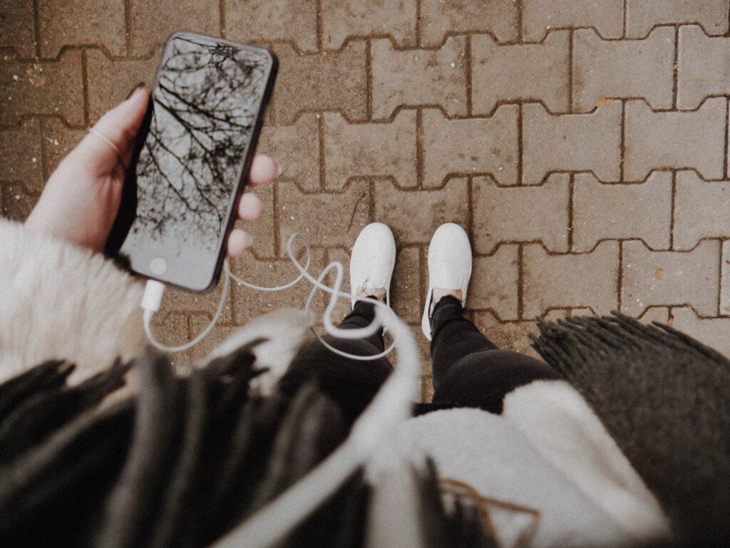 foto dall'alto di una persona che cammina ascoltando un podcast