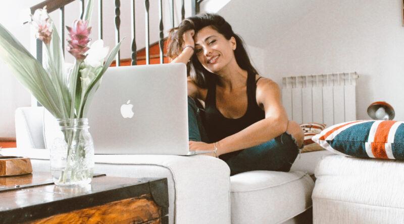 sabrina seduta sul divano con computer guarda in camera e sorride
