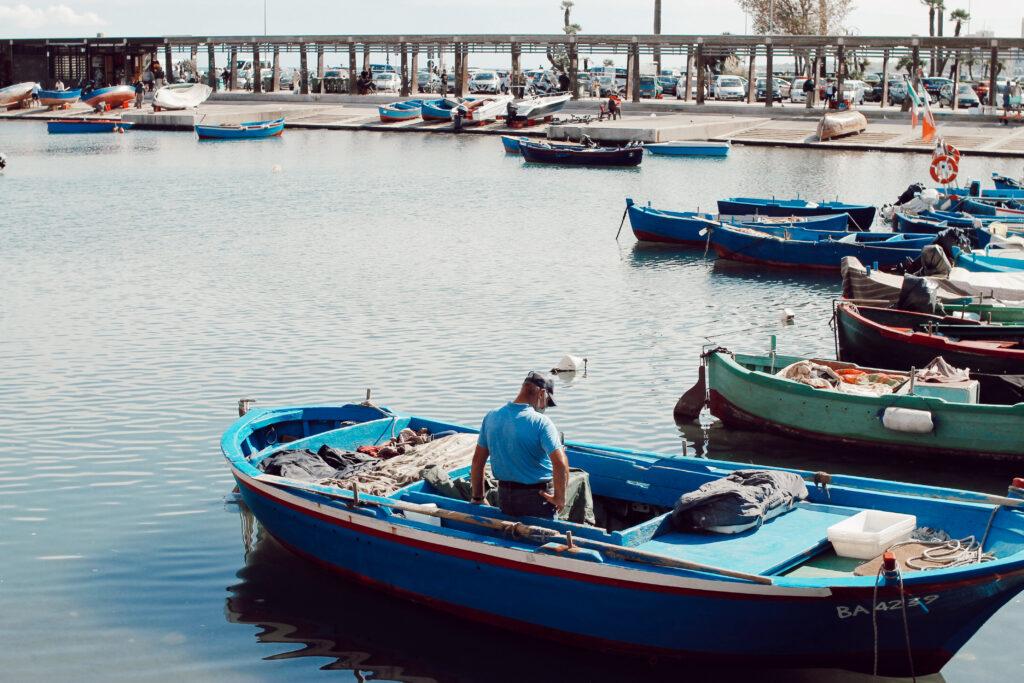 Pescatore sulla barca al porto del mercato del pesce