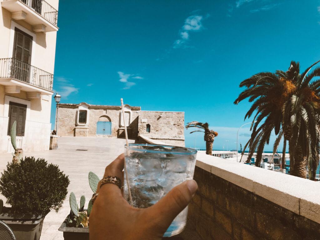 Fortino con cielo azzurro di sfondo e gin tonic in primo piano
