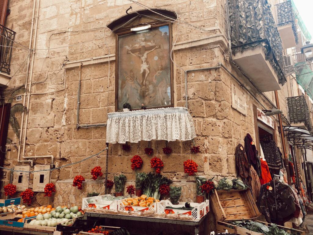 Fruttivendolo sotto una nicchia votiva a Bari vecchia