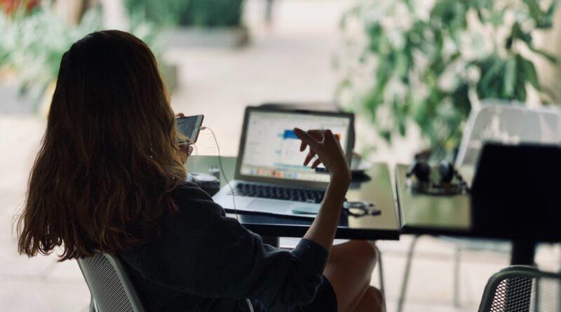 donna che parla al telefonino con un computer davanti. di spalle, castana.