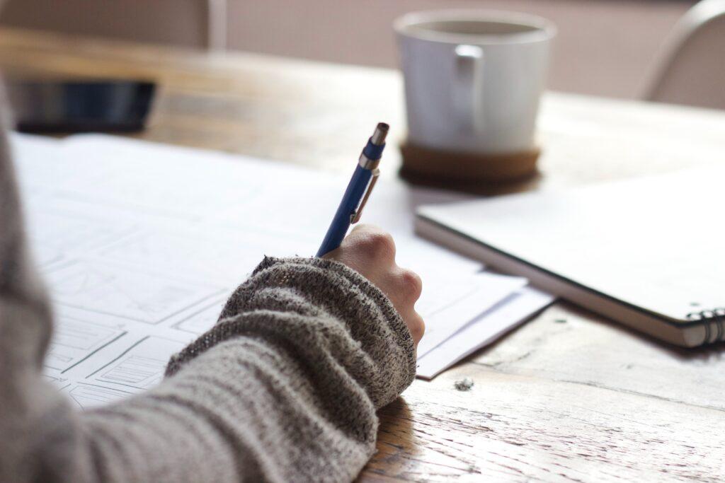 mano che scrive su un foglio, tazza sullo sfondo
