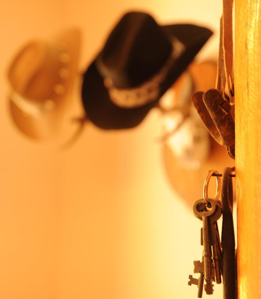 cappello nero e cappello bianco appesi e chiavi in primo piano